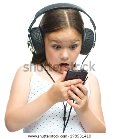 Cute little girl is enjoying music using headphones, isolated over white