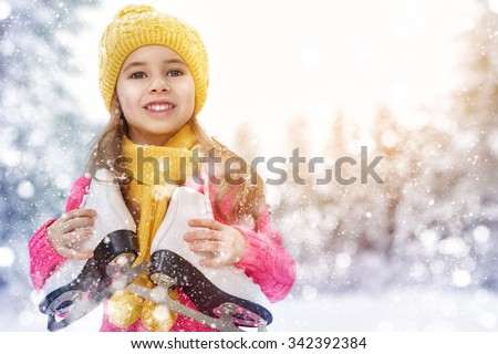 cute little girl is going skate outdoors - stock photo
