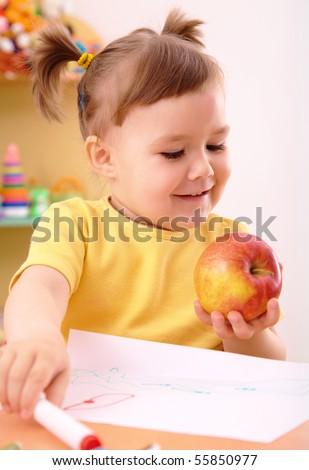 Cute little girl is going to eat apple in preschool - stock photo
