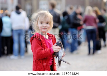 Cute little girl is holding a pigeon - stock photo