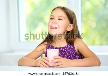 Cute little girl is licking her lips while drinking milk - stock photo
