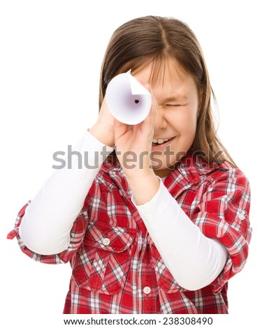 Cute little girl is looking through spyglass made of paper, isolated over white - stock photo