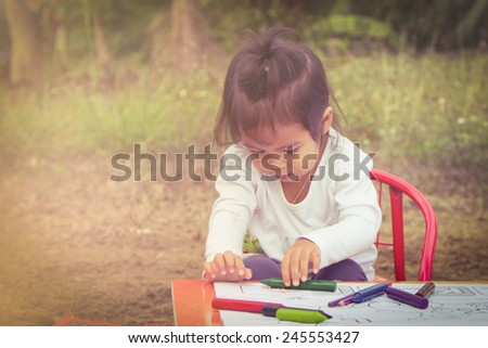 Cute little girl is painting in garden in soft style