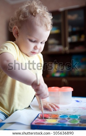 Cute little girl is painting with colorful paints