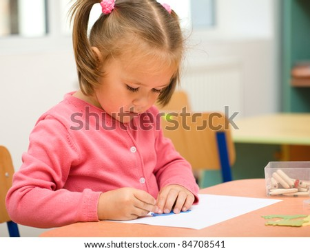 Cute little girl is play with pencils in preschool