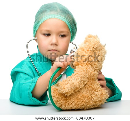 Cute little girl is playing doctor with stethoscope and teddy bear, isolated over white - stock photo