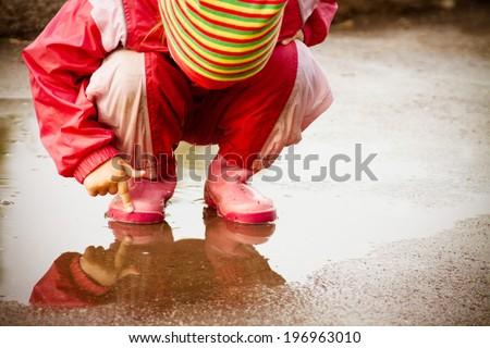 cute little girl is playing in muddy puddles - stock photo