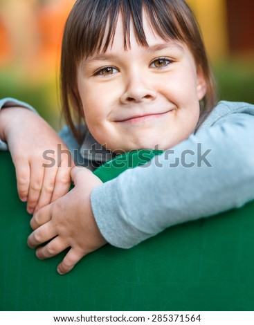 Cute little girl is playing in playground, closeup shoot, outdoor - stock photo