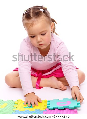 Cute little girl is playing with alphabet while sitting on floor, isolated over white