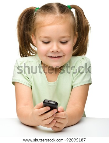 Cute little girl is playing with cell phone while sitting at table, isolated over white