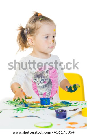 Cute little girl is playing with colored paints isolated on white background