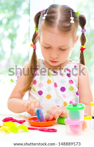 cute little girl is playing with  colorful play dough