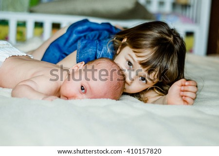 Cute little girl is playing with his younger brother at home lying on the bed with cups