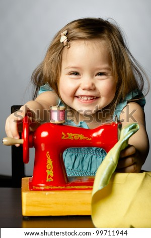 Cute little girl is playing with sewing machine - stock photo