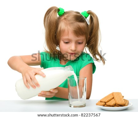 Cute little girl is pouring milk in glass, isolated over white - stock photo
