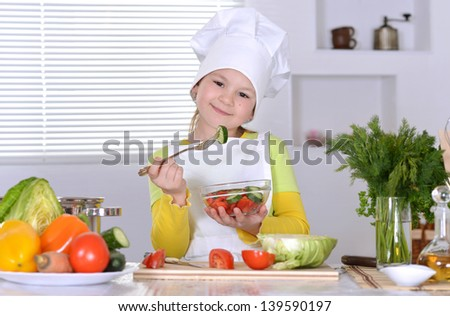 cute little girl is preparing salad in the kitchen at home
