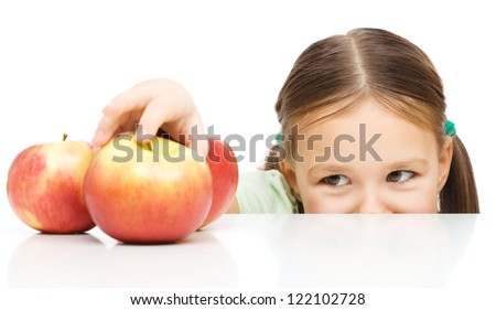 Cute little girl is reaching apple on table, isolated over white - stock photo