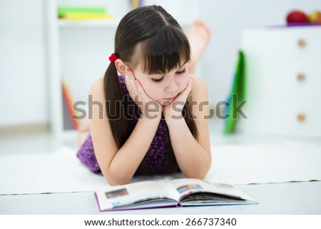 Cute little girl is reading a book - stock photo