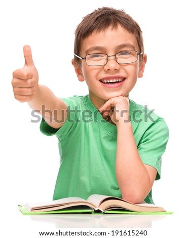 Cute little girl is reading a book and showing thumb up sign, isolated over white - stock photo