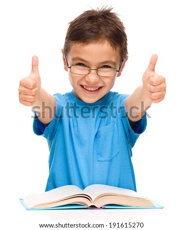 Cute little girl is reading a book and showing thumb up sign using both hands, isolated over white - stock photo