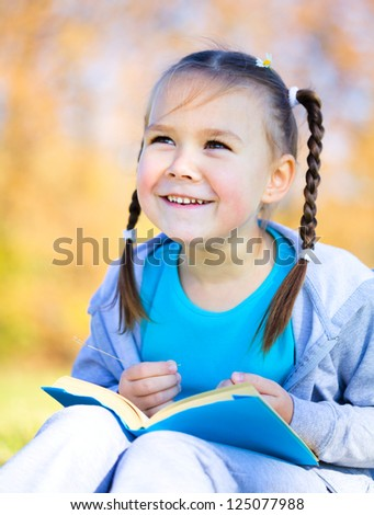 Cute little girl is reading a book outdoors - stock photo