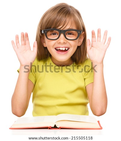 Cute little girl is reading a book while wearing glasses and showing hands, isolated over white - stock photo
