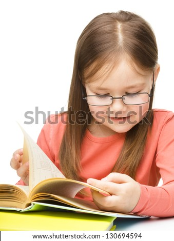 Cute little girl is reading a book while wearing glasses, isolated over white - stock photo