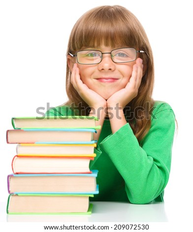 Cute little girl is reading a book while wearing glasses supporting his head with hands, isolated over white - stock photo