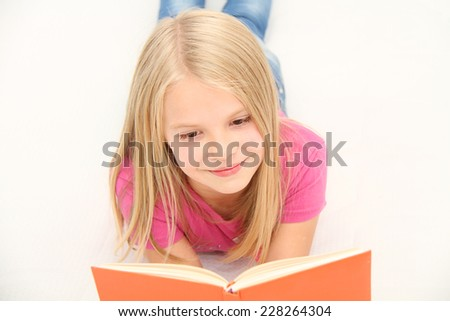 Cute little girl is reading book - stock photo