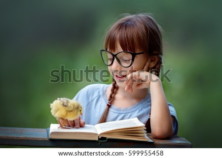 Cute little girl is reading the book with her friends chickens. Education concept