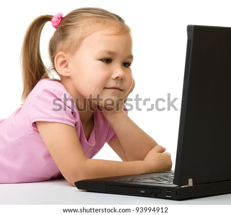 Cute little girl is sitting at table with her black laptop, isolated over white - stock photo