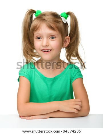 Cute little girl is sitting at the table in astonishment, isolated over white
