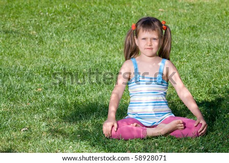 Cute little girl is sitting in yoga lotus asana under tree shadow on the green grass - stock photo