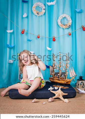 Cute little girl is sitting on a mattress on the sea background scenery, shell keeps hand near ear and smiling - stock photo
