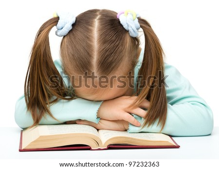 Cute little girl is sleeping on a book, isolated over white