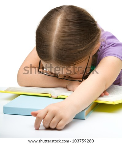 Cute little girl is sleeping on a book while wearing glasses, isolated over white - stock photo