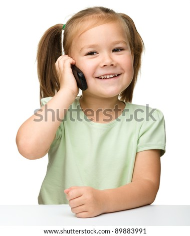 Cute little girl is talking on cell phone while sitting at table, isolated over white - stock photo