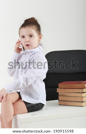 Cute little girl is talking on cell phone while sitting on the t - stock photo