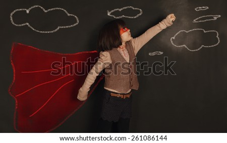 cute little girl is using her imagination to become a super hero - stock photo
