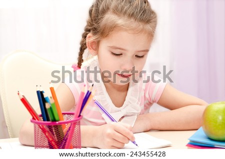 Cute little girl is writing at the desk at home - stock photo