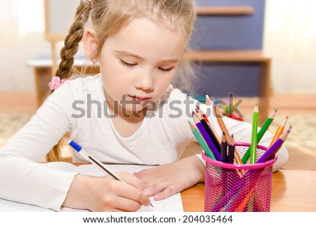 Cute little girl is writing at the desk  in preschool - stock photo