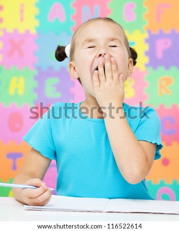 Cute little girl is yawning while writing something using a pen in preschool - stock photo