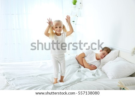 Cute little girl jumping on bed while her elder brother is sleeping