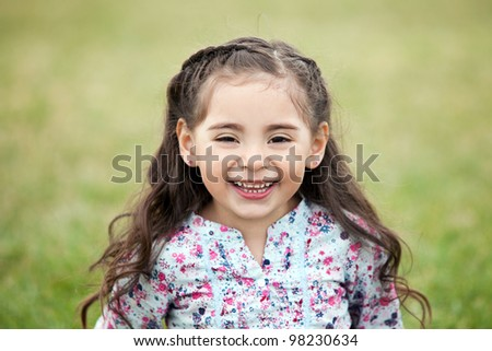Cute little girl laughing outside - stock photo