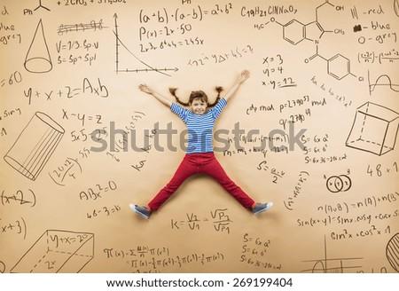 Cute little girl learning playfully in frot of a big blackboard. Studio shot on beige background. - stock photo