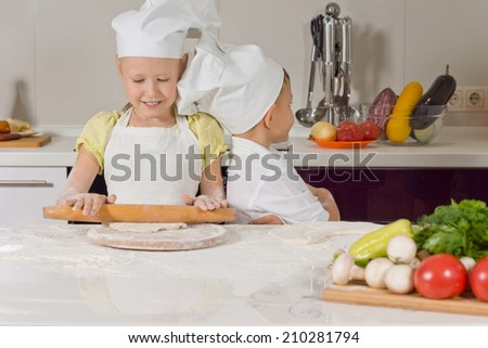 Cute little girl learning to bake in her cooks uniform standing at the kitchen counter rolling out dough with a rolling pin - stock photo