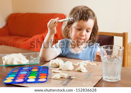 Cute little girl learning to paint dough figurines in the room