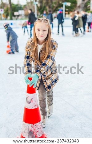Cute little girl learning to skate with the support on a nice winter day