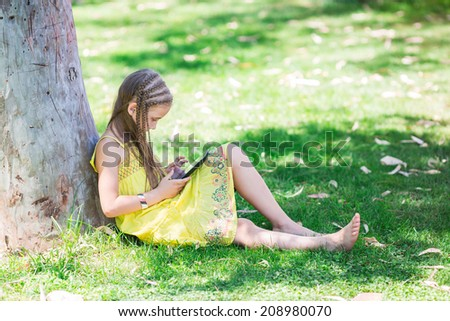 Cute little girl learning with tablet pc in the park - stock photo