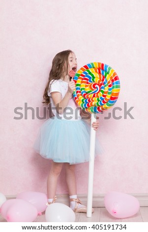 cute little girl lick huge lollipop in one hand and hold small lollipop in other hand - stock photo